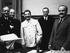 Podpis paktu o neútočení. Sovětský ministr zahraničí Vjačeslav Molotov (vpravo) a jeho německý protějšek Joachim von Ribbentrop (vlevo) při podpisu paktu o neútočení 23. srpna 1939 v Moskvě. Uprostřed se usmívá J. V. Stalin.