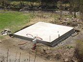 Montovaný dům lze postavit i za pár dnů - Nejdříve se připraví základové pásy v nezámrzné hloubce, což je minimálně 1 metr. Přes vrchní líc základových pásů přijde betonová plošná deska.