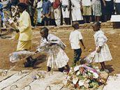 Děti kladou květiny v místě masového hrobu v Kicukiru.