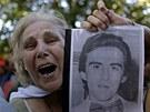 Pozůstalí ukazují fotografie svých příbuzných, kteří zemřeli při takzvané špinavé válce