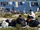 Uprchlíci z Tuniska věší prádlo na ostrově Lampedusa, na italském ostrově jich je téměř šest tisíc