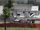 Pákistánský voják stojí před sídlem Usámy bin Ládina v Abbottábádu (2. května 2011)