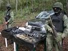 Mexičtí vojáci stojí u munice a vysílaček, které po přestřelce objevili ve