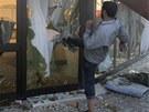 Libyjský povstalec rozbíjí sklo v jedné z budov Kaddáfího komplexu Báb...