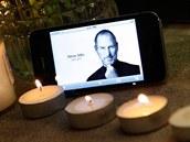 Svíčky a portrét Steva Jobse na displeji iPhonu před obchodem Apple v New