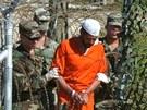 Američtí vojáci vedou trestance ve věznici Guantánamo. (1. března 2002)