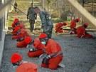 Trestanci čekají na dvoře věznice Guantánamo. (11. ledna 2002)