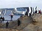Zvědavci okukují vrak lodi Costa Concordia, která ztroskotala u italského ostrova Giglio. (22. ledna 2012)