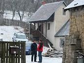 Policisté hlídkují u domu v Doubravách na Zlínsku. Zbraně našli v budově vzadu.