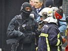 Francouzský policista ze zásahové jednotky a hasiči nedaleko domu, ve kterém se