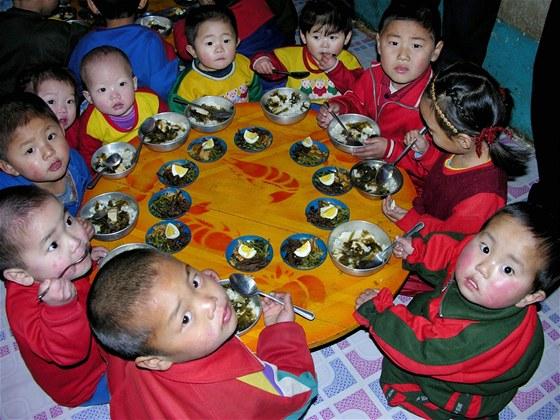 Oběd severokorejských dětí ve školce na snímku dokládajícím využití