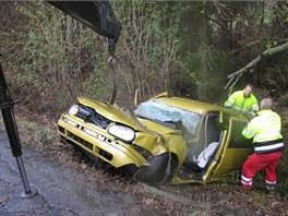 Vytahování zdemolovaného auta z lesa u cesty, kde po smyku, převrácení a