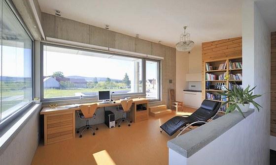 V pracovně se pohledový beton snoubí s bílým štukem, borovicovým dřevem a