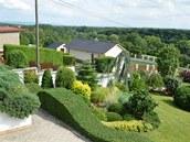 Netradiční zvlněný tvar živého plotu na úrovni spodní terasy pod domem se