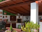 Pod střechou pavilonu, která je skloněná mírně dozadu, se nabízí posezení pro