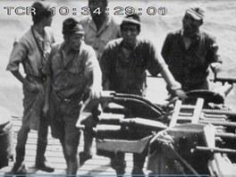 Posádka japonské ponorky u protiletadlového trojkanonu na stropě hangáru