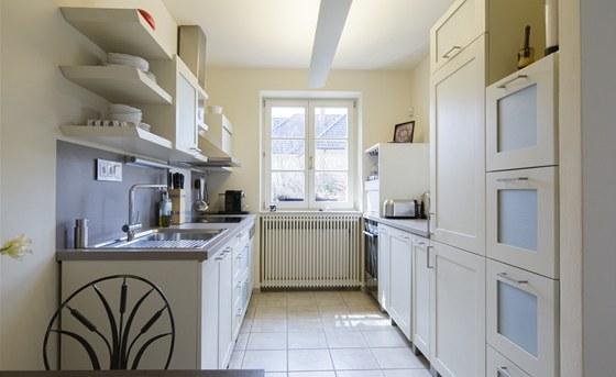 Poměrně malý prostor kuchyně opticky zvětšuje použitá barevnost, částečně