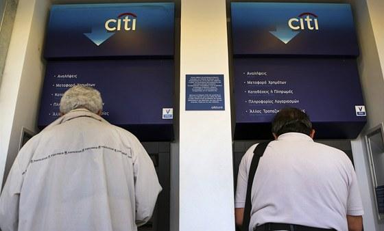 Dva muži vybírají peníze v centru Atén. Bojí se o své úspory. Řecko čekají nové