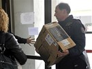 Policisté přinášejí krabici s důkazy do sídla Útvaru pro odhalování