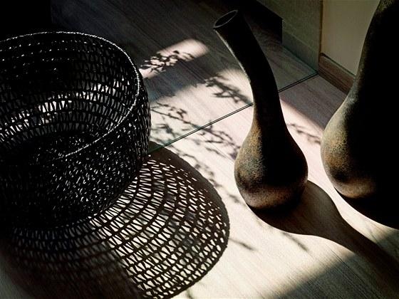 Dopadající světlo vytváří na dřevěné podlaze zajímavé obrazce, které návrhářku