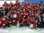 VÍT�ZNÉ FOTO. �e�tí hokejisté a realiza�ní tým pózují fotograf�m s bronzovými...