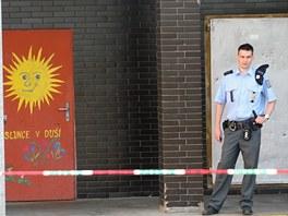 Policista hlídá u jednoho ze vchodů do Základní školy Moravská v