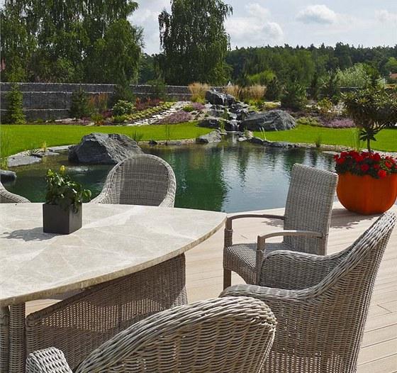 Rozměrná terasa s pohodlným nábytkem je jako stvořená pro relaxaci u vody.