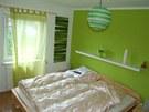 Lo�nici je lad�n� do syt� zelen� barvy v kombinaci se d�evem.