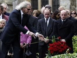 Hudebník Barry Gibb pokládá růži na hrob při pohřbu zesnulého bratra Robina.