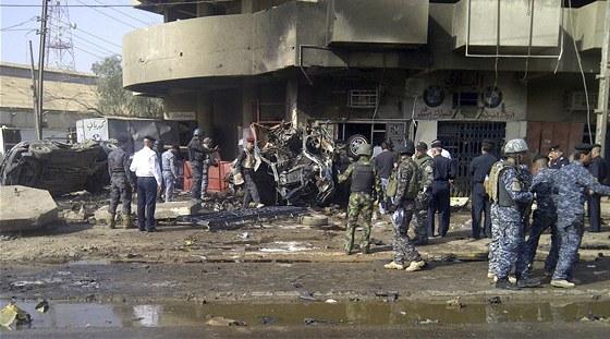 Vojáci a policisté stojí u ohořelých vraků aut, která vybuchla v Bagdádu (13.