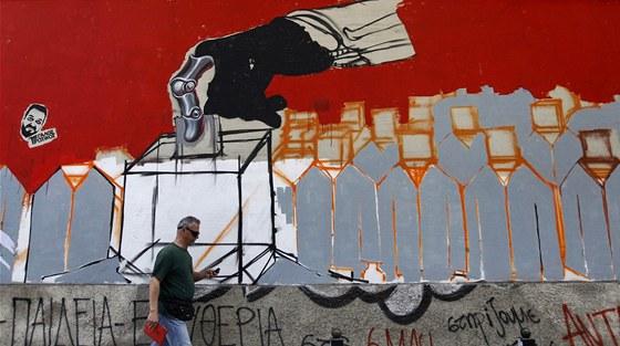 �ek proch�z� v At�n�ch kolem opu�t�n� budovy s grafitti odkazuj�c�m na