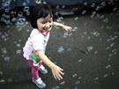 D�v�átko si v centru Hongkongu neru�en� hraje s bublinkami, zatímco okolo n�j...