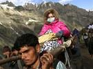 Ka�mír�tí nosi�i p�ená�ejí poutnici z Indie b�hem tradi�ní cesty do jeskyn�...