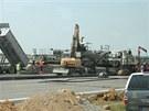 Finišer, stroj o váze 155 tun, zajišťuje položení svrchní cementobetonové
