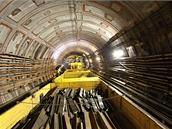 Do třetího vozíku ukládají dělníci vytěžené kusy kolejnic. Mají délku do metru...