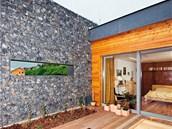 Terasa. Kámen a dřevo spolu s ozeleněnou střechou napomáhají splynutí