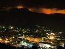 Noční pohled na město La Jonquera, v pozadí je vidět záře z požáru (22.