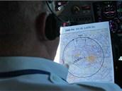 Pilot studuje mapku s plánem letu.