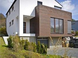 Těleso obložené tmavě mořeným dřevem naznačuje umístění hlavní společné obývací