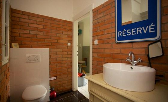 V koupelně s toaletou použil designér obklad z cihlových pásků.