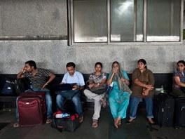 Indičtí pasažéři čekají na vlak po masivním výpadku elektřiny, který postihl