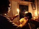 TMA NEVADÍ. Indický holi� z Kalkaty dr�í v jedné ruce sví�ku a druhou st�íhá...