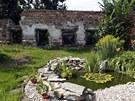 Zahrada zámečku působí malebně. Rozpadlé stěny v pozadí však celkový dojem kazí.