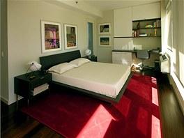 V ložnici dodává barevný akcent malinový koberec. Našel se zde i prostor na