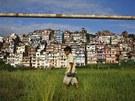 MEZI NEBEM A ZEMÍ. Nepálský chlapec se brouzdá travou na zarostlém fotbalovém...