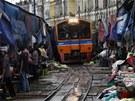 VLAK NA TR�I�TI. Thaj�tí trhovci sklízejí své zbo�í p�ed projí�d�jícím vlakem....