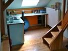 Pohled na pracovní část dívčího pokoje se stolem a nízkou skříňkou na míru.