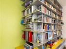 """Dominanta celého bytu - policová knihovna """"prorůstá"""" do ložnice v podobě"""