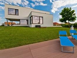 Dům stojí na vyvýšené části pozemku, terasa u bazénu je z materiálu Twinson.