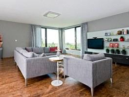 Obývací pokoj zatepluje opticky laminátová podlaha Quick step s dřevinovým